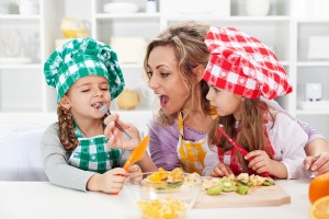 Woman and little girls tasting salad ingredients